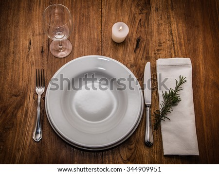 informal but elegant table setting whit white plates, cutlery, white towel, glass, white candle lit on old wooden table - stock photo