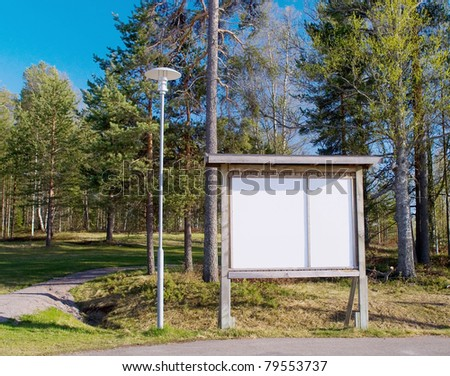 Information empty white bilboard near the path in the park - stock photo