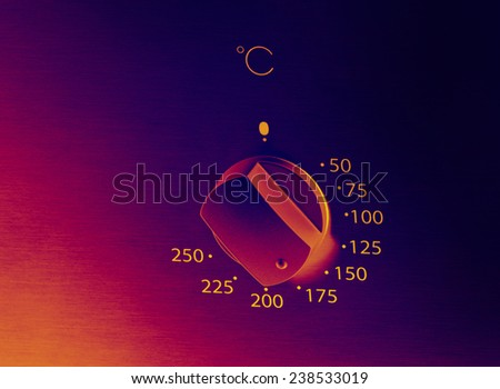 Infrared image of oven knob on silver board - stock photo