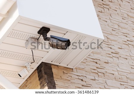 Infrared security day and night cameras on wall of house covered with lite brown decorative slate stone wall surface.  - stock photo