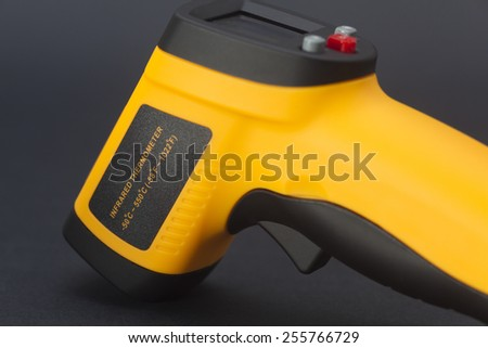Infrared thermometer in black background - stock photo