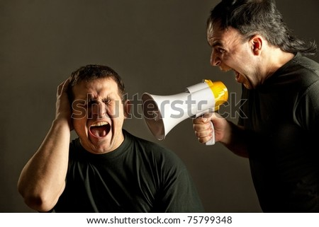 Infuriated man yelling with a megaphone at other man - stock photo