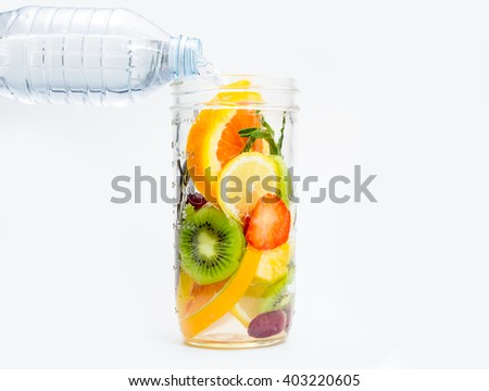Infused water with fresh organic berries and fruits on white background - stock photo