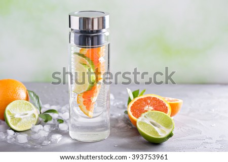 Infused water with orange and lime in a bottle - stock photo