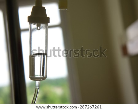 Infusion bottle with IV intravenous solution in hospital - stock photo