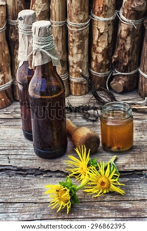 infusion of inflorescences and roots of the medicinal plant Inula on the wooden table next mortar and pestle.Photo tinted. - stock photo