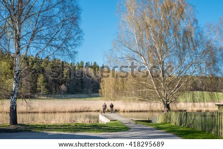 INGARO, SWEDEN - MAY 5: People fish during spring on May 5, 2016 in Ingaro outside Stockholm. Springtime in Sweden is fresh, green and flowering with long bright days. - stock photo