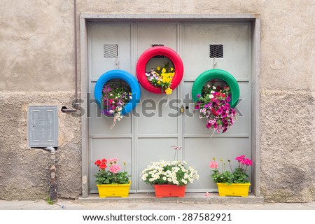 Ingenious, original and environmentally friendly method of recycling of tires car as planters in a village in Tuscany. - stock photo