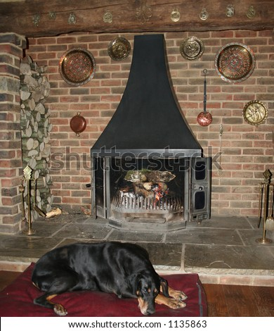 Inglenook fireplace with open fire and sleeping dog in front of it  = Home ( focus on fire) - stock photo