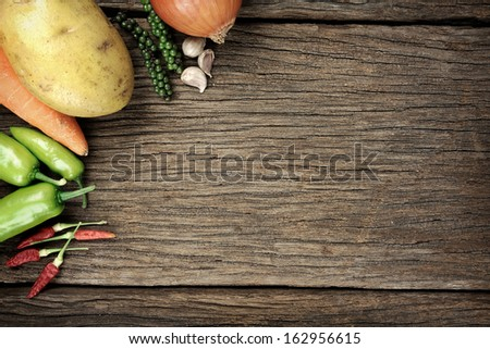 ingredient background, fresh vegetables and herbs on ancient wooden table - stock photo