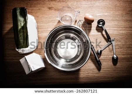 Ingredients, a bowl, and some cooking utensils are gathered together for making something. - stock photo