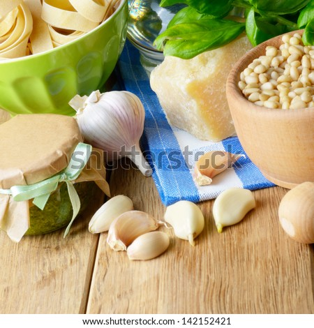 Ingredients and pesto sauce on the kitchen table - stock photo