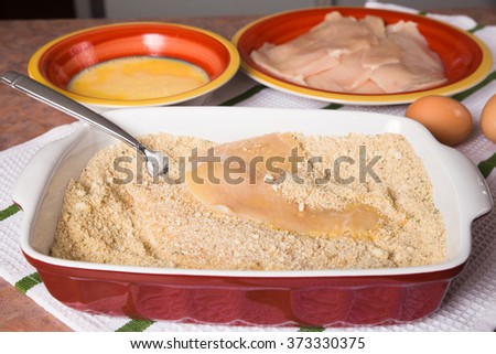 Ingredients and preparation of Italian style chicken breast cutlets with breadcrumbs and eggs  - stock photo