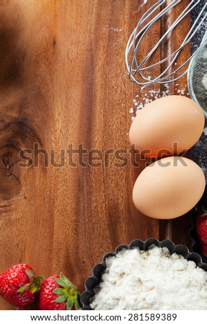 Ingredients and tools for baking - flour, eggs, rolling pin and fresh berries on the black background, top view - stock photo
