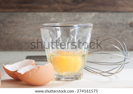 ingredients and tools to make a cake, eggs, bakery cups on wood table