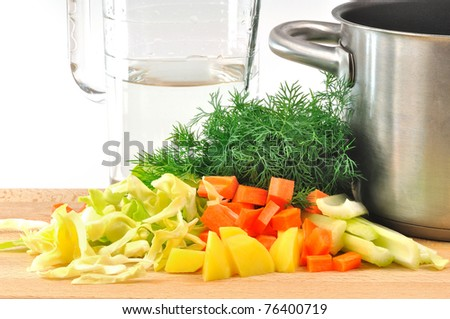 INGREDIENTS cabbage soup CUT vegetables on a board with the pots and jug of water - stock photo