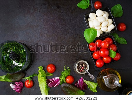 Ingredients Caprese salad tomato and mozzarella with basil and herbs oon black background. Top view - stock photo