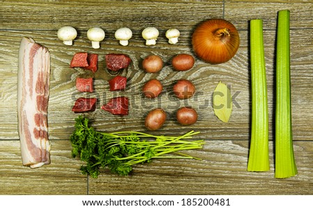 Ingredients for a beef stew on a wood table - stock photo