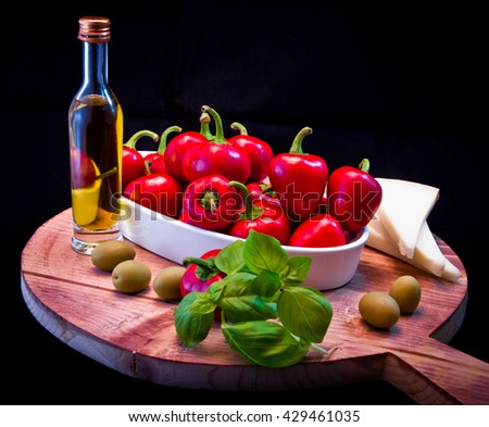Ingredients for a Mediterranean sauce for pasta, bruschetta, salad or sandwich with olive oil, peppers, basil, cheese, figs and olives, ideal for a fresh and healthy meal in summer - stock photo