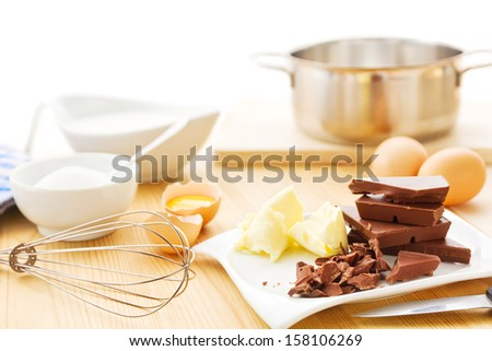 Ingredients for a mousse au chocolat including dark chocolate, eggs, butter, cream and sugar - stock photo