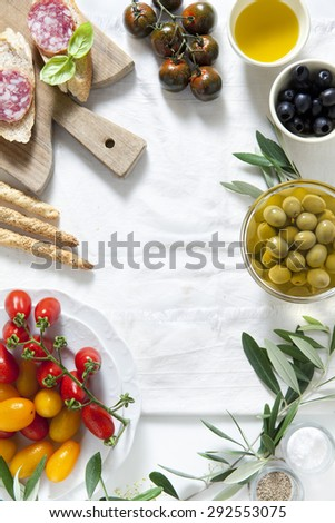 ingredients for a summer snack. summer products. sandwich with salami, red and yellow Grape Tomatoes, green and black olives, black zebra cherry tomato, bread sticks and olive oil. - stock photo