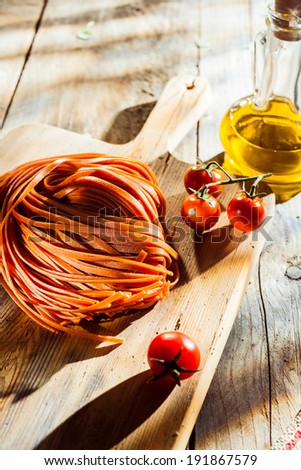 Ingredients for a tasty Italian tomato pasta dish with flavored linguine pasta. cherry tomatoes and olive oil on a chopping board on a rustoc wooden kitchen table - stock photo