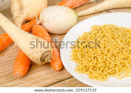 Ingredients for a vegetable soup on a rustic wooden table - stock photo