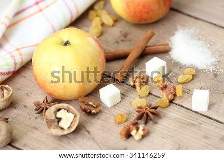 Ingredients for apple pie cooking. Fresh apples, sugar, cinnamon, raisin and nuts on a wooden table. - stock photo