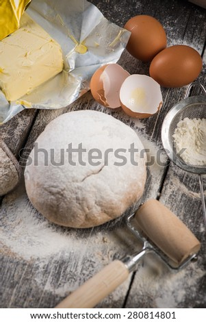 Ingredients for baking and homemade dough on wooden table