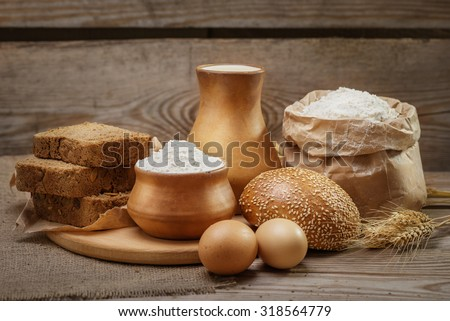 Ingredients for baking bread and pastry, milk, wheat flour, eggs, bun with sesame, rustic bread, cut into pieces, ears of wheat on the old wooden background - stock photo