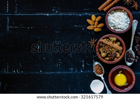 Ingredients for baking cake (flour, egg, brown sugar) in wooden bowls on dark vintage background with space for text. Top view. - stock photo