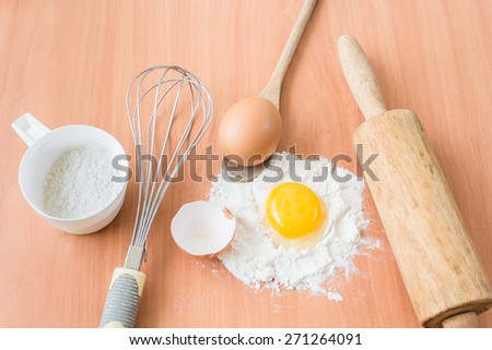 Ingredients for baking cake with egg on a wooden worktop - stock photo