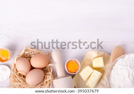 Ingredients for baking croissants - flour, wooden spoon, rolling pin, eggs, egg yolks, butter served on white background. - stock photo