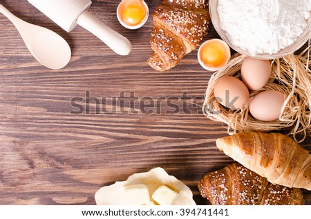 Ingredients for baking croissants - paper, flour, wooden spoon, rolling pin, eggs, egg yolks, butter served on a rustic wooden tray table.  - stock photo
