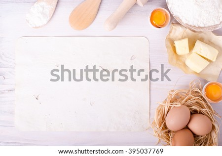 Ingredients for baking croissants - paper, flour, wooden spoon, rolling pin, eggs, egg yolks, butter served on white background. - stock photo