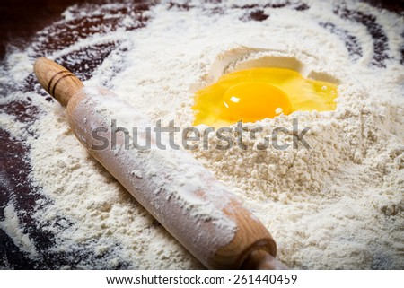 Ingredients for baking - flour, egg and rolling pin on dark wooden table - stock photo