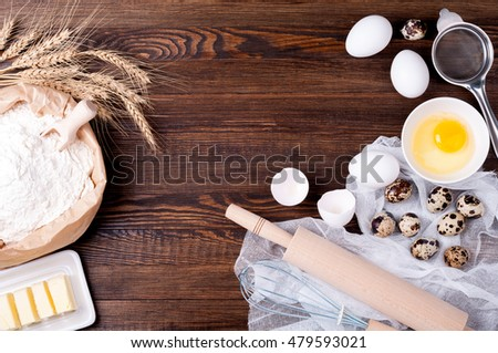 Ingredients for baking. Flour in paper bag, eggs, butter, rolling pin and whisk on wooden background. Cooking bread, cake or cookies. Copy space. Top view