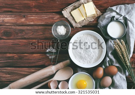 Ingredients for baking - flour, milk, eggs, butter. View from above. Rustic background with free text space. Ingredients for the dough. Food background - stock photo