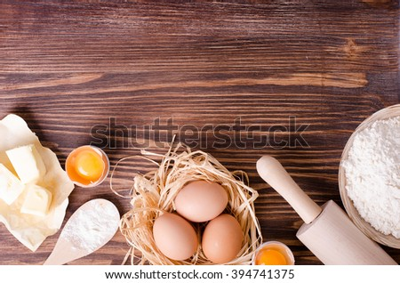 Ingredients for baking - flour, wooden spoon, rolling pin, eggs, egg yolks, butter on vintage wood table from above. Rustic background with free text space. - stock photo