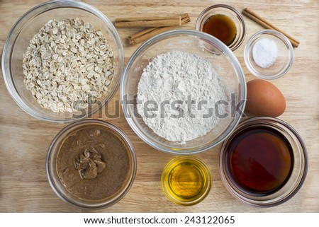 Ingredients for baking healthy oatmeal cookies including maple syrup. - stock photo