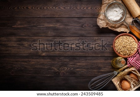 Ingredients for baking including eggs, oils, grains and flour, with sieve and whisk flour on empty wooden background with place for your text or recipes. - stock photo