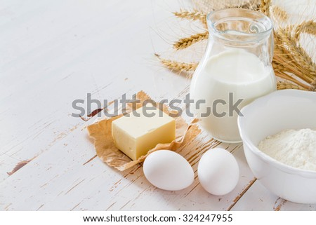 Ingredients for baking - milk butter eggs flour wheat, white wood background, copy space - stock photo