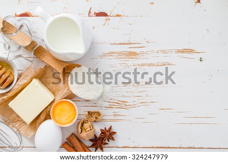 Ingredients for baking - milk butter eggs flour wheat, white wood background, copy space, top view - stock photo