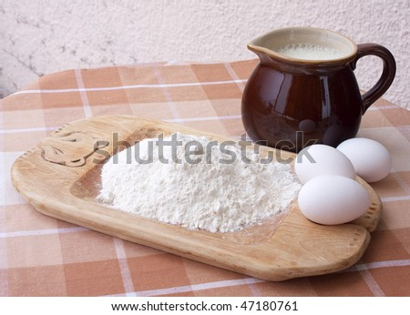 Ingredients for baking on table top: eggs, milk and flour