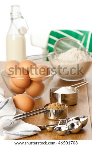 Ingredients for baking on table top with apron thrown over back of chair in background - stock photo