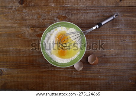Ingredients for baking on wooden table top with yolk in flour copyspace, horizontal picture - stock photo