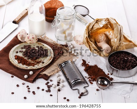 Ingredients for baking with chocolate: choc chips and cocoa powder over white wooden background. Selective focus - stock photo