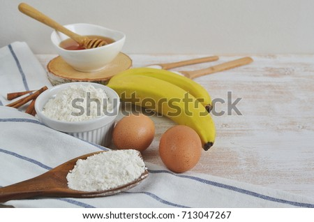 Ingredients for Banana Pancakes Preparation Baking Accessories Kitchen Composition Wooden Table Top Metal Whisk Wooden Spoon Bananas Eggs Milk