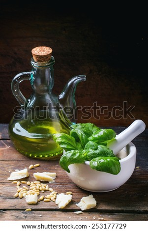 Ingredients for basil pesto served with white mortar over old wooden table. - stock photo