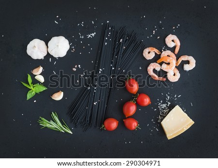 Ingredients for black pasta with seafood. Shrimps, spaghetti, basil, garlic, spices, parmesan cheese and  cherry-tomatoes on dark grunge backdrop, top view, - stock photo
